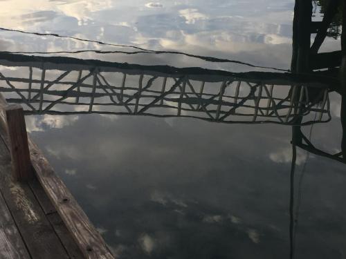 glassy water reflects gangplank